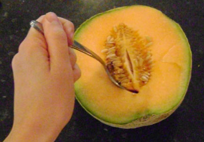 Scoop out the seeds from a cantalope with a spoon