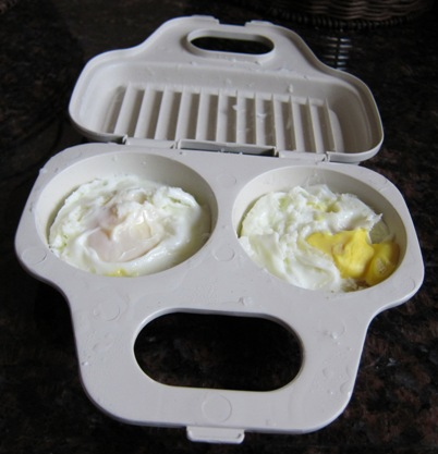cooked eggs inside the microwaveable egg poacher