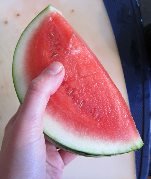 hand holding a slice of red, sweet and juicy watermelon