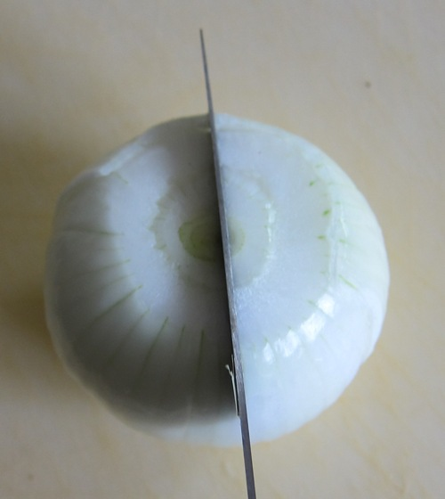 cutting onion in half with a knife