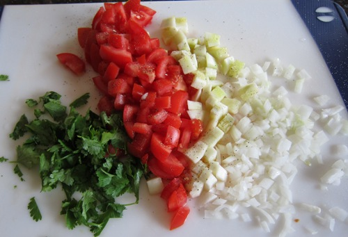 cut up tomatoes, cucumbers, onions and cilantro on cutting board