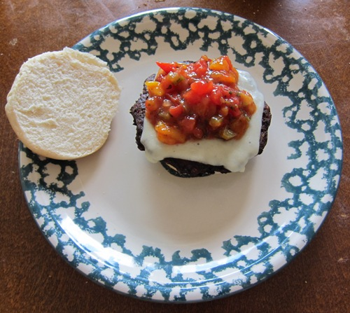 making black bean cheeseburger with salsa, cheese and veggie patty