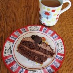 a slice of chocolate truffle cake on a plate and a cup of coffee