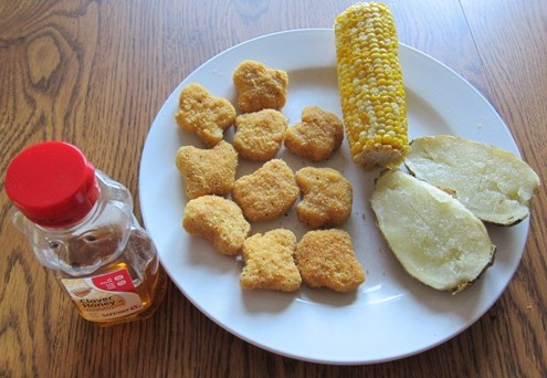 chicken nuggets, corn on the cob and baked potato