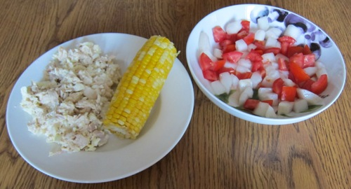 chicken salad, corn on the cob and cucumber salad