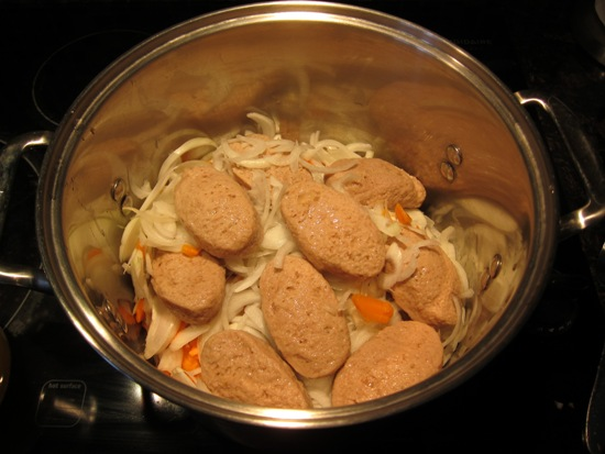 jarred gefilte fish in a pot with onions and carrots