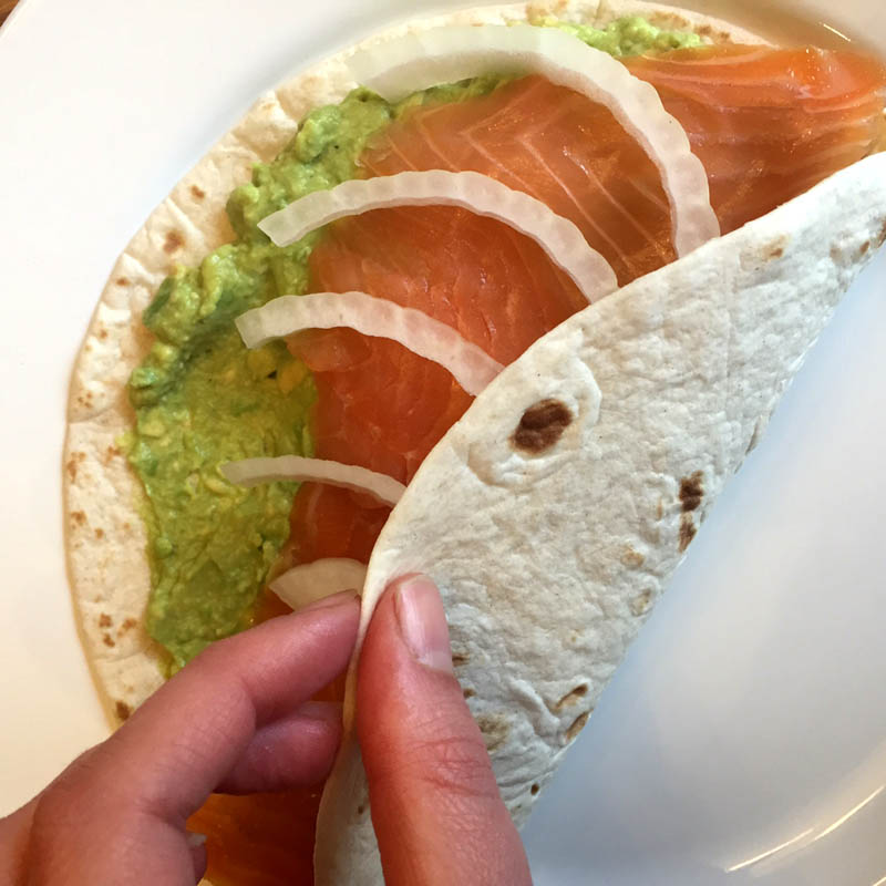 Rolling the smoked salmon and avocado tortilla wrap