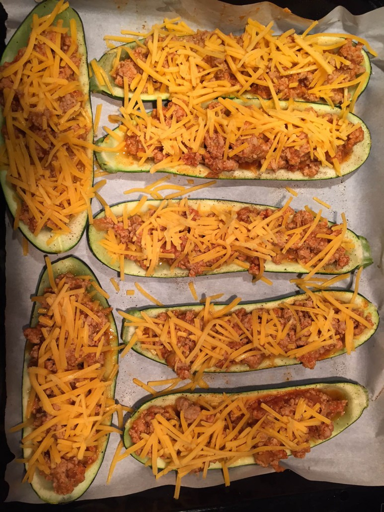 Sprinkle stuffed zucchini boats with shredded cheese