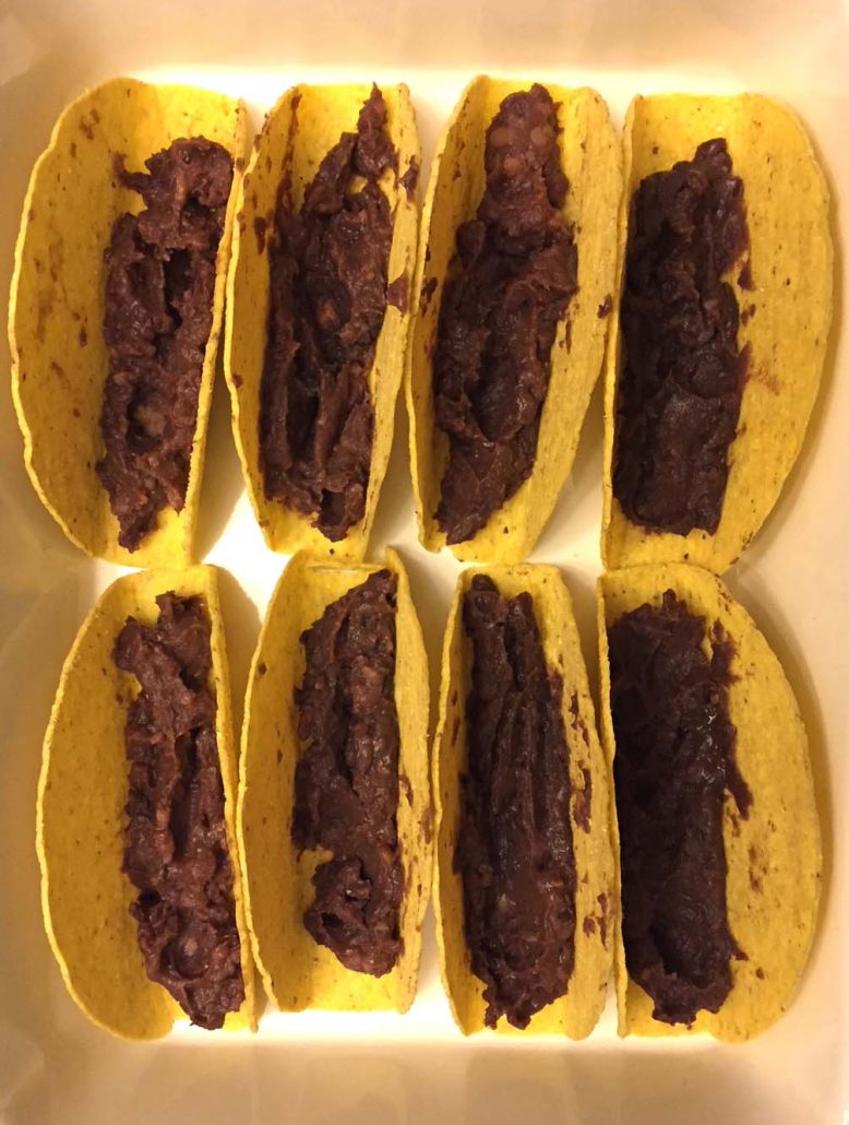 refried beans in the taco shells