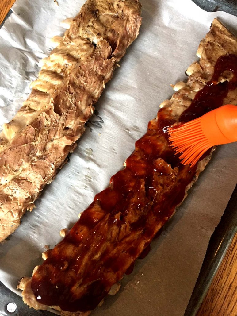 Brushing ribs with BBQ sauce