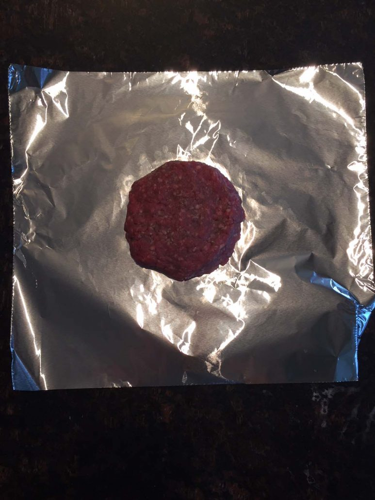Hamburger patty on foil