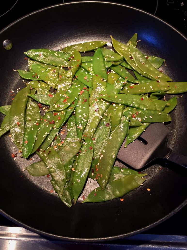 Spicy Garlic Sesame Snow Peas In A Frying Pan