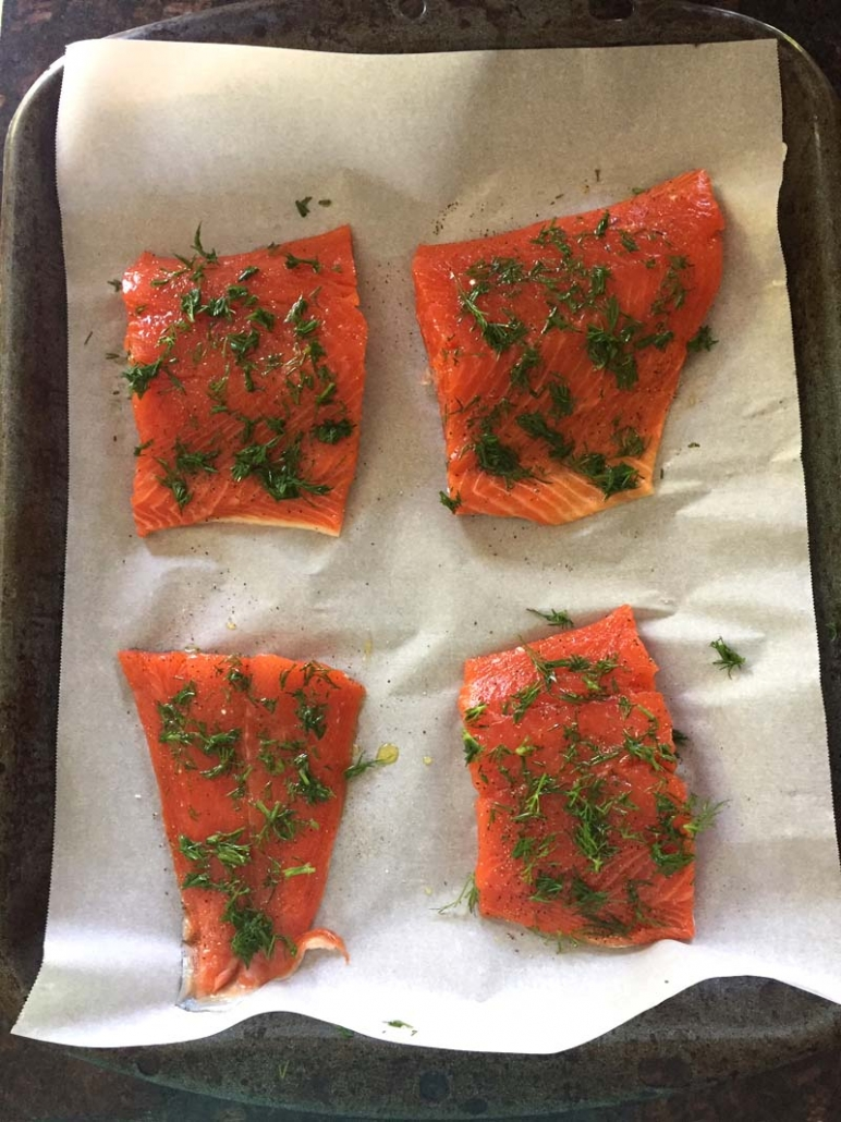 salmon fillets with dill on baking sheet