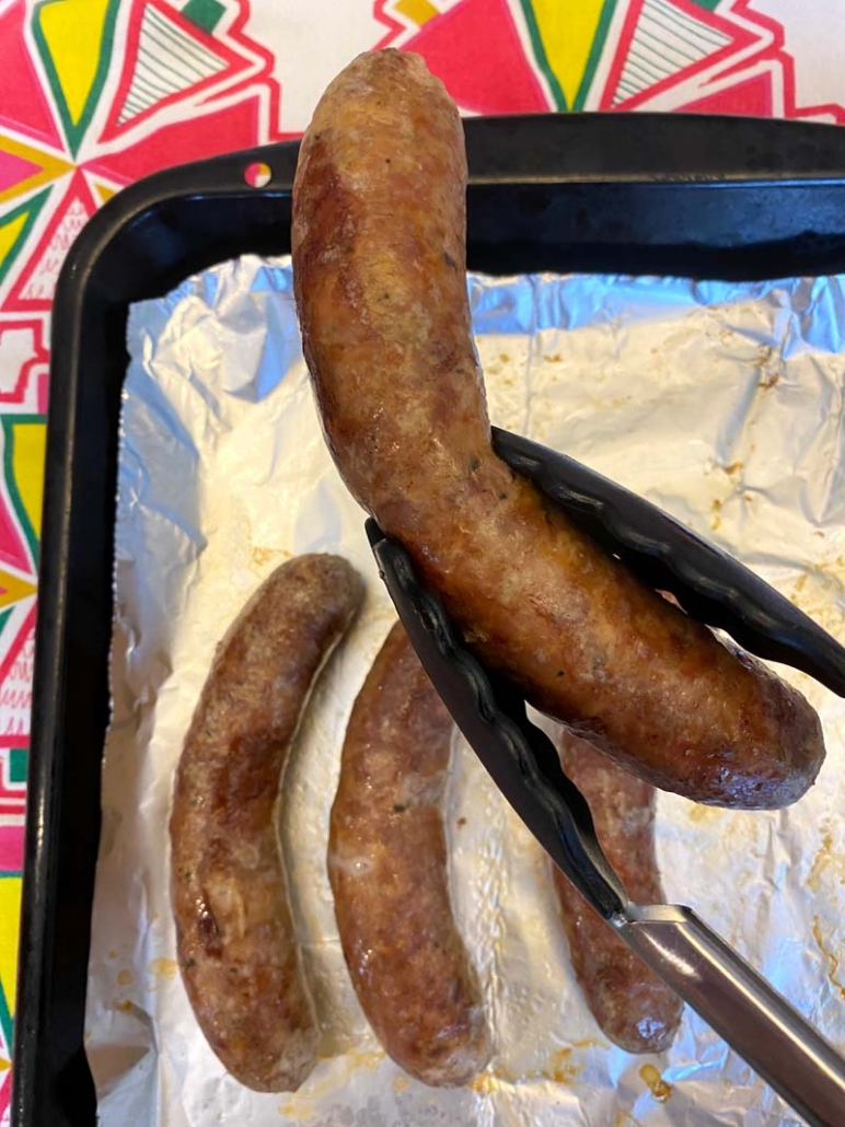 picking up an italian sausage with tongs